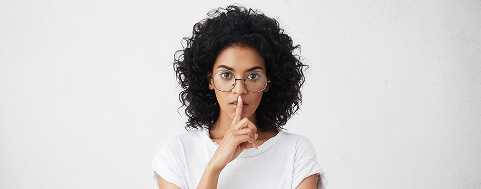 Woman silencing with a finger on lips