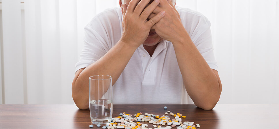 depressed senior man with pills on desk