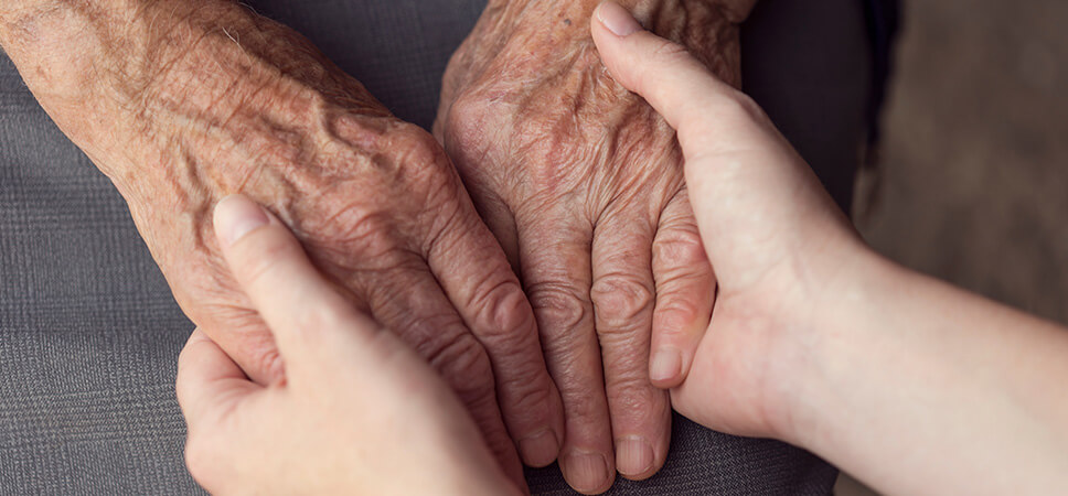 young person holding senior's hands