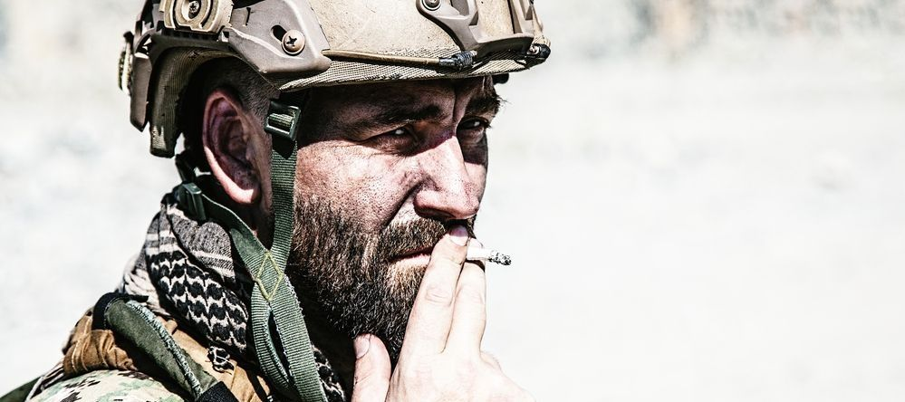 An equipped soldier smoking a cigarette