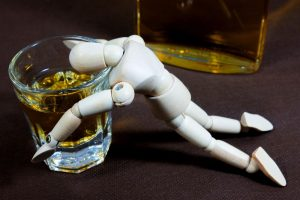 A toy demonstrating alcohol addiction with a glass
