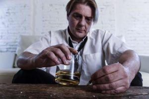 Sad alcoholic businessman drinking whiskey and smoking at home