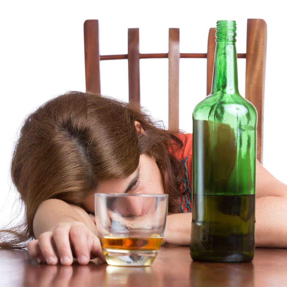 Drunk and tired woman with a bottle of scotch isolated on white
