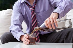 Young man drinking whisky alone at home