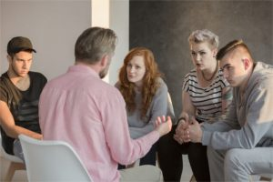 Addiction counselor talking to group of his teenage patients