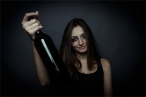 Young unhappy woman holds alcohol bottle