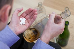 Addicted man mixing pills with an alcohol