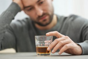 Lonely depressed man drinking whisky at home