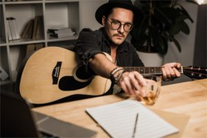 young unsuccessful musician with acoustic guitar drinking whiskey at workplace