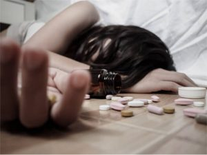 Young woman is lying on the floor with a lot of pills