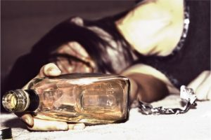 drunk woman lying on the floor, bottle of whiskey in the hand