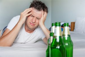 Hangover suffering man holding his aching head close up portrait with bottles of beer