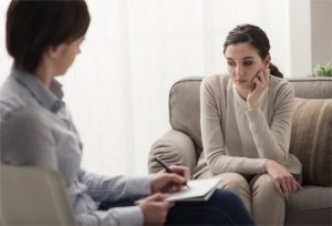 Young female patient talking with her therapist in the office