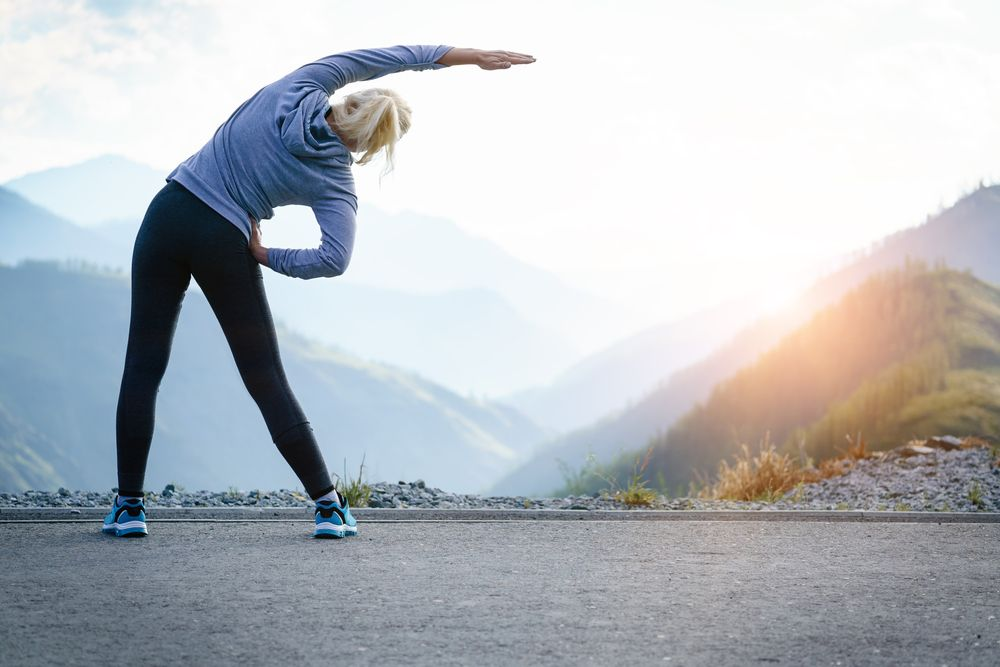 Woman exercising near mountain.