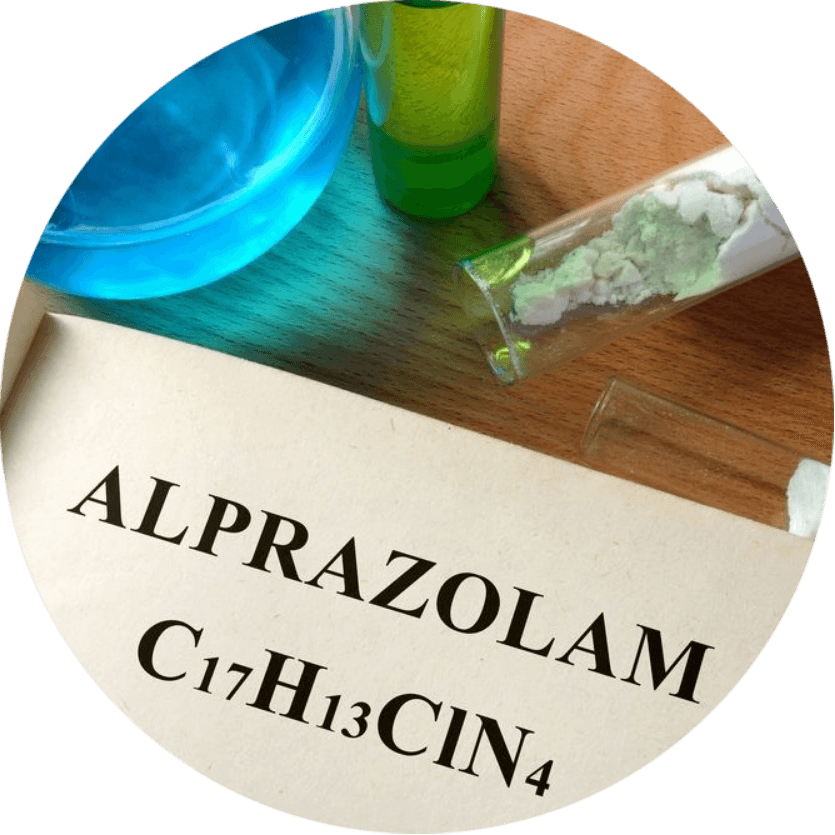 Book on a table with a page written alprazolam and showing its chemical formula