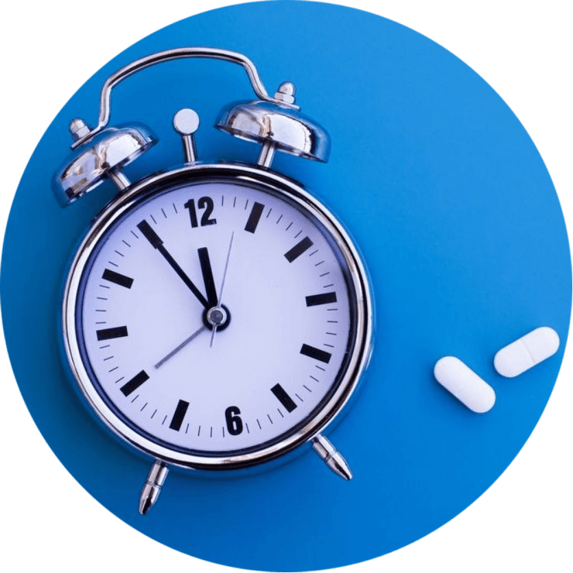 Alarm clock on a blue surface with Xanax pills beside it.