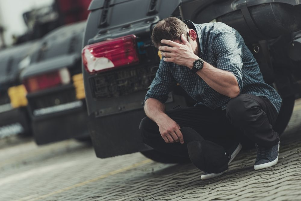 Man crouching and in shock behind vehicles in a car park.