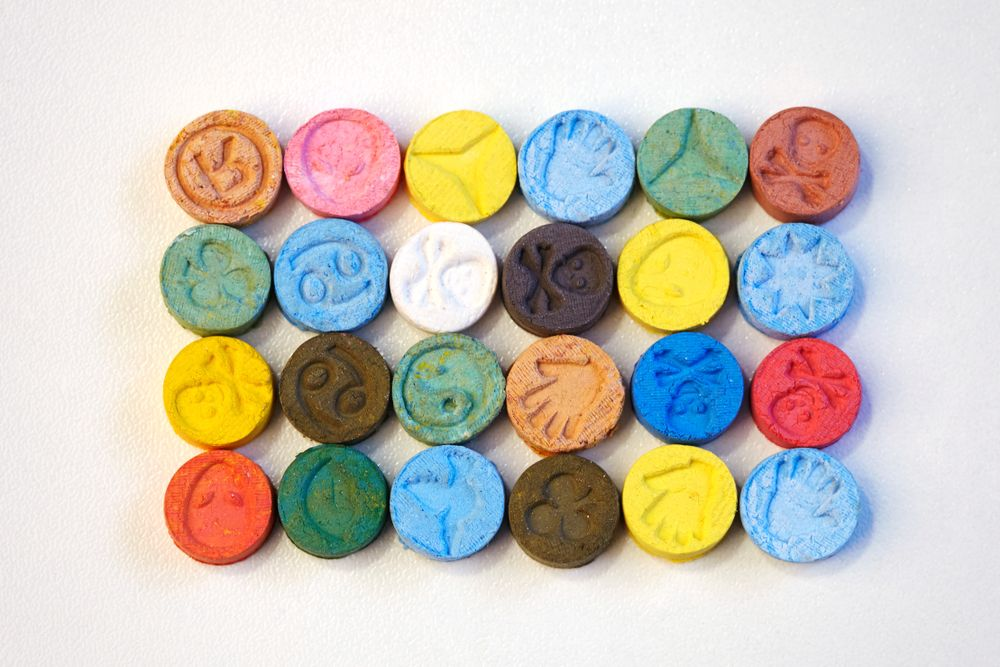 Different-colored ecstasy pills on the table