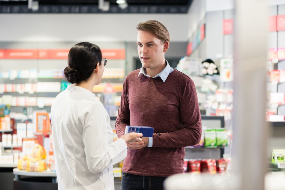 A pharmacist goes over contraindications and interactions of a medication with a customer.
