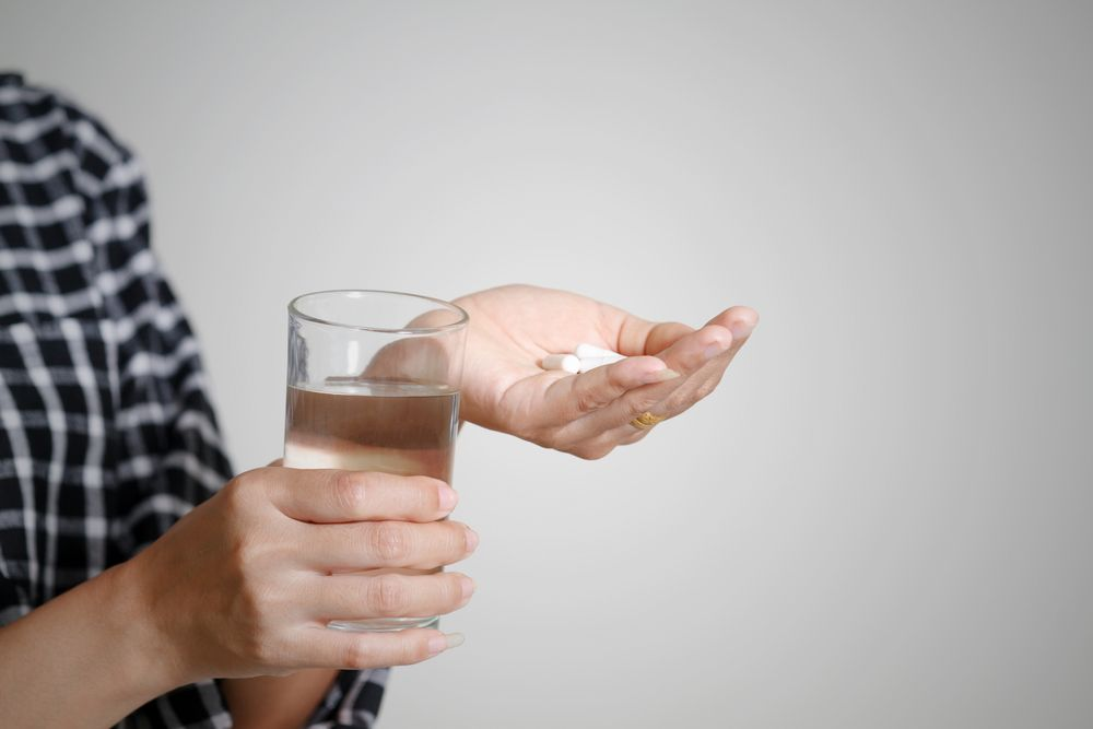 Lady taking alprazolam pills with some water