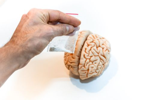 hand holding a drug bag with a brain in the background