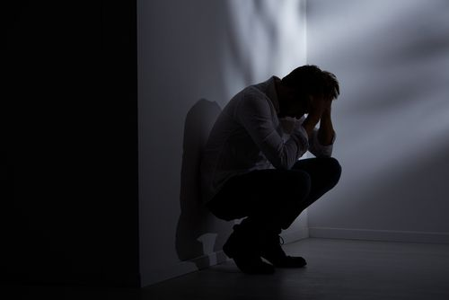 Abandoned and lost man sitting beside wall in dark room.