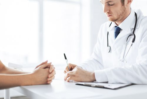 Doctor in a white lab coat talking to morphine addiction patient while taking notes.