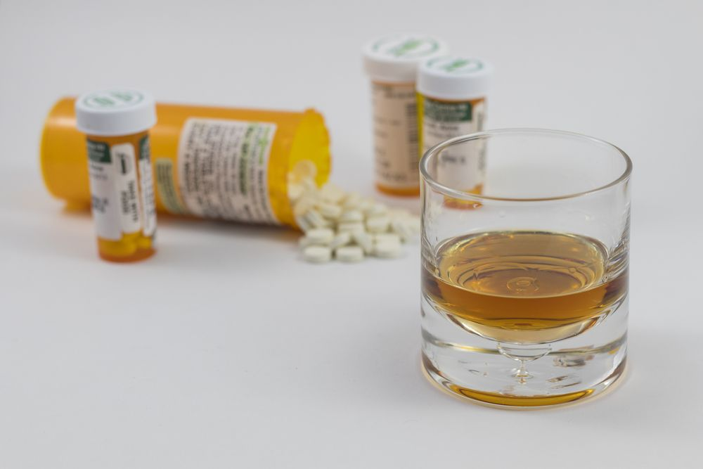 Alcohol and Gabapentin pills on a white table surface.