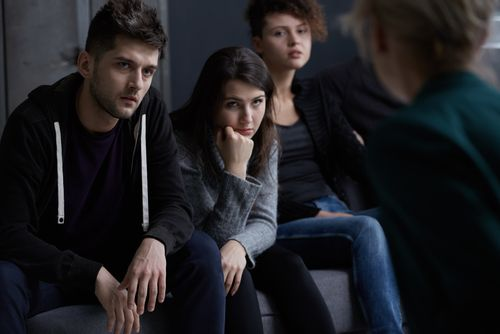 Patients listening to a counselor during a group therapy session at a drug rehab center.