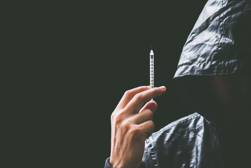 Hooded drug addict holding syringe over black background.