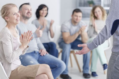 Man standing in front of applauding support group after making progress.