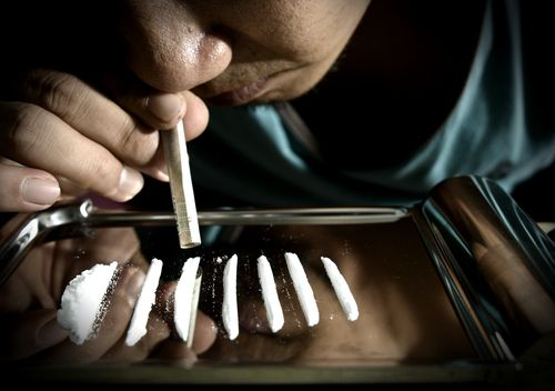 Man snorts cocaine with rolled up banknote