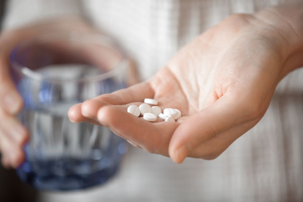 Person holding a glass of water with one hand and Klonopin pills with the other.