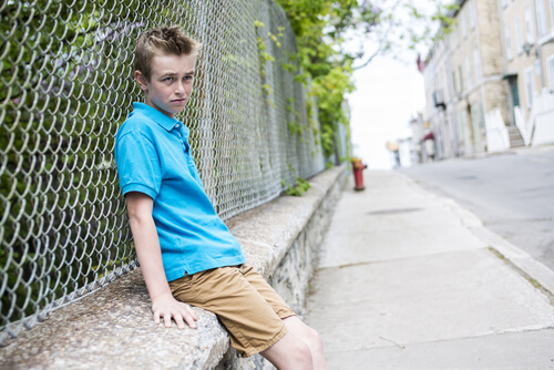 troubled teen sitting near a fence