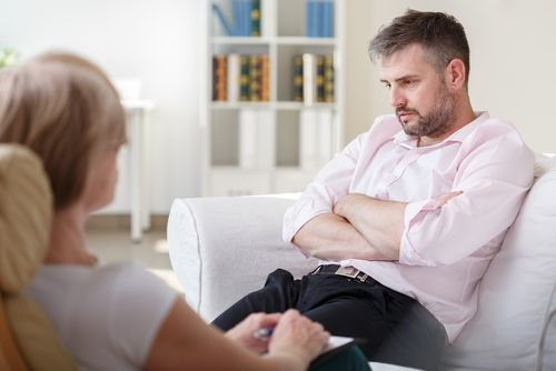 Addicted businessman talking with psychiatrist on psychotherapy session.