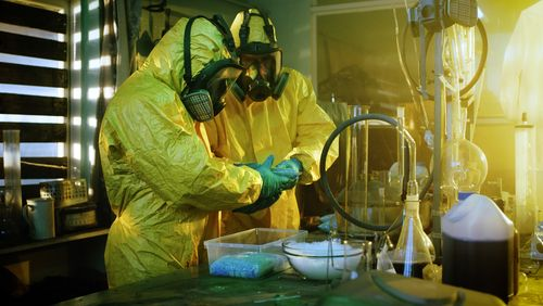 Two people are producing drugs at the laboratory.