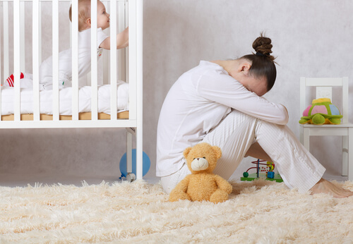 sad depressed young mother sitting near the newborn's bed