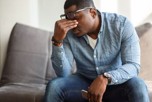 Frustrated young black man massaging his nose and keeping eyes closed.