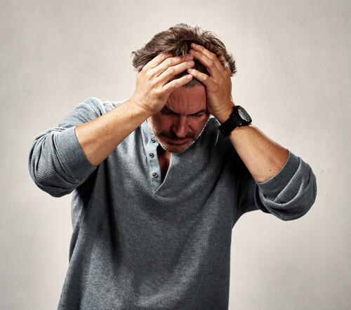 depressed man with headache holding his head in hands
