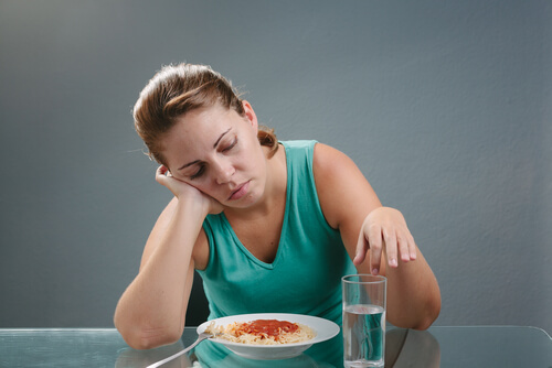 sad woman sitting in front of the meal with no appertite