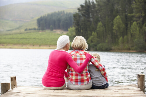 mother, daughter, and grandmother sitting together near the lake