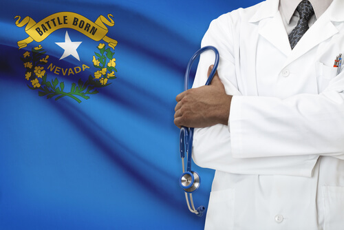 doctor in a unifrom standing at the Nevada state flag