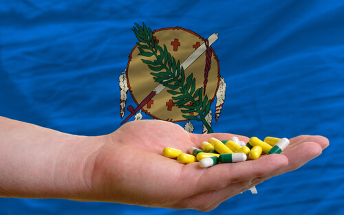 man holding a handful of pills with Oklahoma state flag on the background