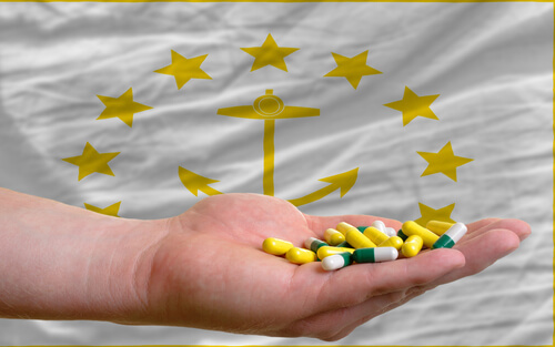 rhode island state flag and a man's hand holding drug capsules