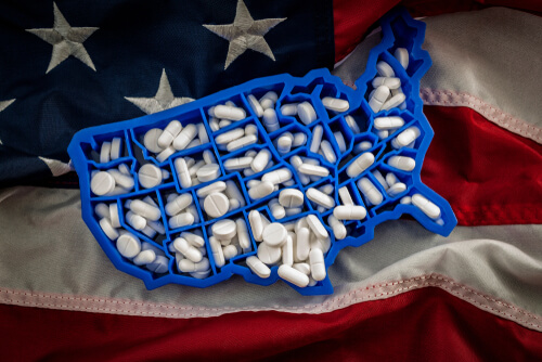 US map filled with Oxycodone and Hydrocodone pills with american flag on the background