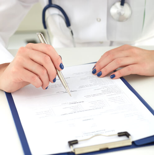 female doctor assessing patient and making notes in medical card