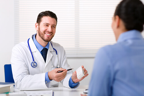 smiling doctor prescibing pills to the patient