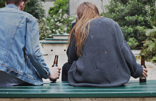 two young people drinking beer on the street sitting on the bench
