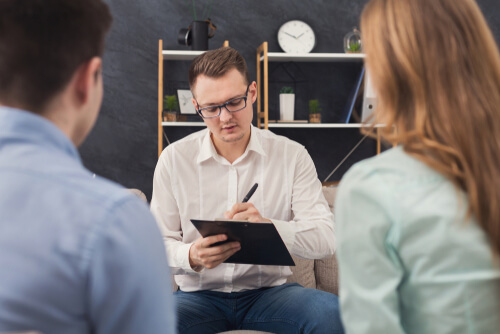 young couple sitting on a couch during family therapy with male therapist sitting in front of them making notes
