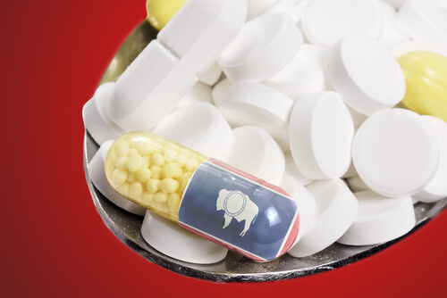 National flag of Wyoming on a capsule and pills on a spoon
